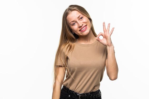 Jonge vrouw met ok gebaar knipogen geïsoleerd op wit oppervlak