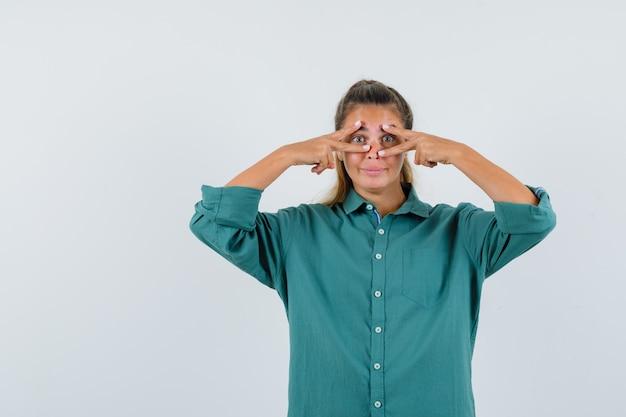 Jonge vrouw met omgekeerde v-teken op haar ogen in blauw shirt vooraanzicht.
