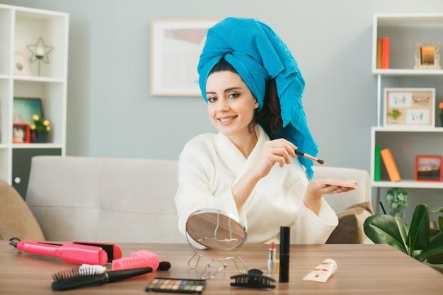 Jonge vrouw met oogschaduwpalet met make-upborstel gewikkeld haar in een handdoek zittend aan tafel met make-uptools in de woonkamer