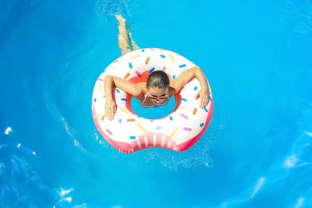 Jonge vrouw met opblaasbare doughnut in zwembad