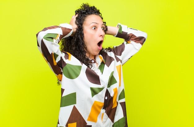 Jonge vrouw met open mond, geschokt en geschokt door een vreselijke fout
