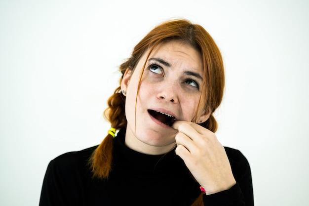 Jonge vrouw met open mond graaft na het eten met haar vingers naar iets dat in de tanden vastzit.