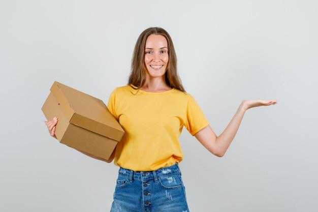 Jonge vrouw met open palm met kartonnen doos in t-shirt, korte broek en op zoek blij