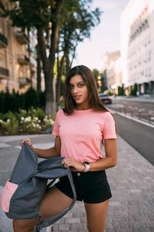 Jonge vrouw met open rugzak op straat. portret van een jonge vrouw