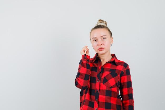 Jonge vrouw met opgeheven arm in geruit overhemd en verstandig kijkt