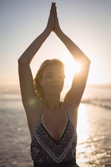 Jonge vrouw met opgeheven armen doet yoga op het strand