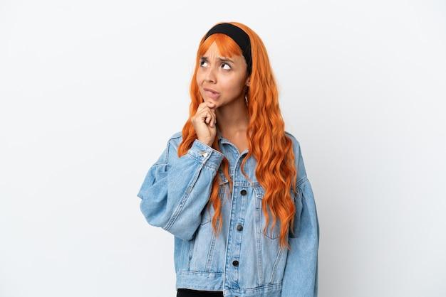 Jonge vrouw met oranje haar geïsoleerd op een witte achtergrond met twijfels en denken