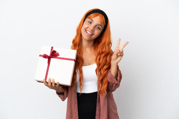 Jonge vrouw met oranje haar met een geschenk geïsoleerd op een witte achtergrond glimlachend en overwinningsteken tonen