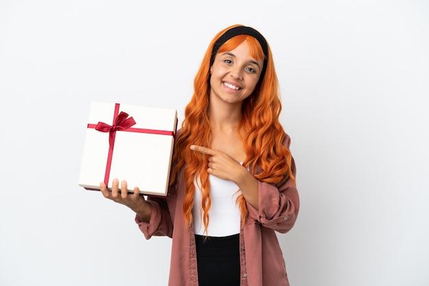 Jonge vrouw met oranje haar met een geschenk geïsoleerd op een witte achtergrond, wijzend naar de zijkant om een product te presenteren