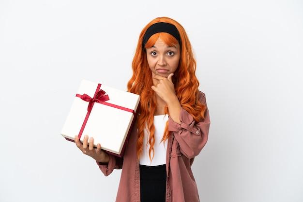 Jonge vrouw met oranje haar met een geschenk geïsoleerd op een witte achtergrond