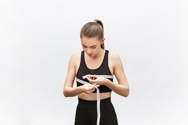 Jonge vrouw met overgewicht in sportieve bovenkant die helaas resultaat van het meten van taille kijkt