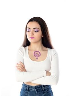Jonge vrouw met paarse make-up en met het feminisme activisme concept tekening op haar lichaam geïsoleerd