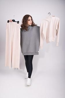 Jonge vrouw met pak op hangers, in een poging om te beslissen wat te dragen