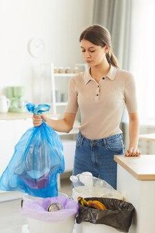 Jonge vrouw met pakket met afval en het in de prullenbak gooien tijdens huishoudelijk werk thuis