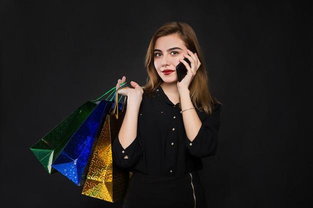 Jonge vrouw met pakketten, aankopen, kortingen