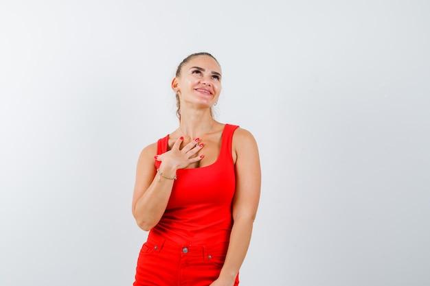 Jonge vrouw met palm op de borst in rood mouwloos onderhemd, broek en op zoek dromerig, vooraanzicht.