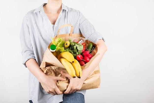 Jonge vrouw met papieren boodschappentassen op grijze ruimte. kopieer ruimte. ruimte voor eten