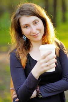 Jonge vrouw met papieren kopje koffie buitenshuis