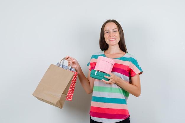 Jonge vrouw met papieren zakken en geschenkdozen in t-shirt, broek en op zoek gelukkig. vooraanzicht.