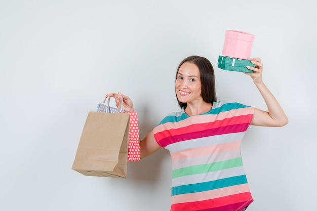 Jonge vrouw met papieren zakken en geschenkdozen in t-shirt en op zoek gelukkig, vooraanzicht.