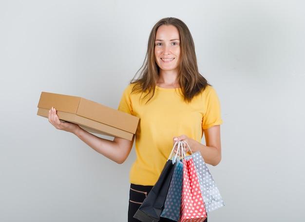 Jonge vrouw met papieren zakken en kartonnen doos in geel t-shirt, broek en op zoek blij
