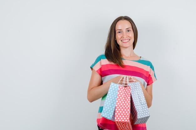 Jonge vrouw met papieren zakken in t-shirt en op zoek vrolijk, vooraanzicht.