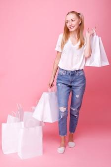 Jonge vrouw met papieren zakken op roze
