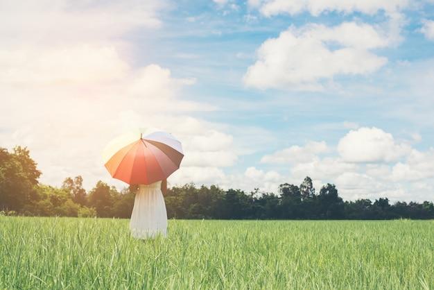 Jonge vrouw met paraplu in de weide
