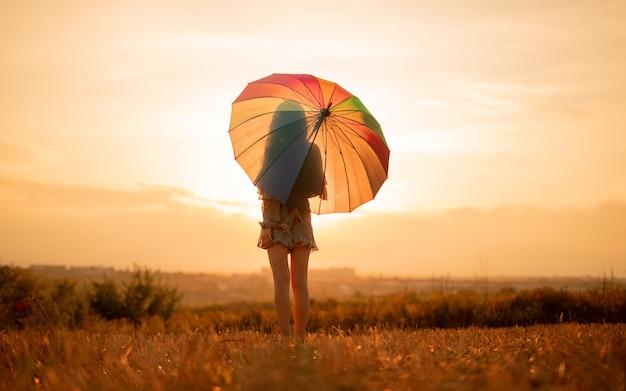 Jonge vrouw met paraplu in het veld