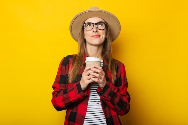 Jonge vrouw met peinzend gezicht in hoed en geruite overhemd die document kop met koffie op gele oppervlakte houden
