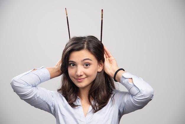 Jonge vrouw met penselen achter haar hoofd. hoge kwaliteit illustratie
