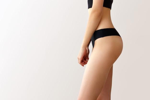 Jonge vrouw met perfecte lichaam op grijze muur. cellulitis probleem concept. liposuctie. mooie vrouwelijke heupen