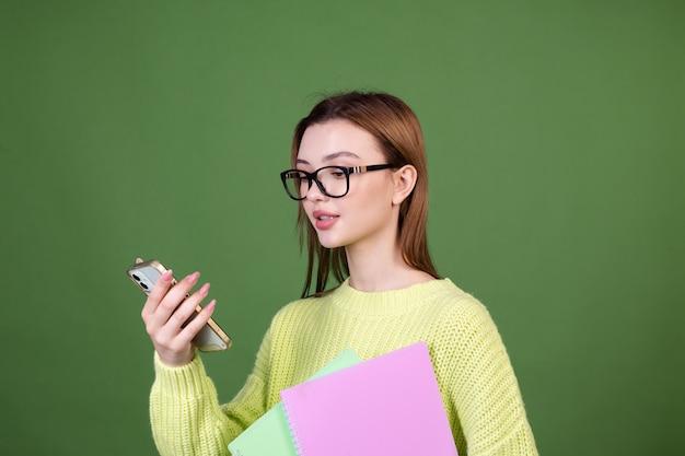 Jonge vrouw met perfecte natuurlijke make-up bruine grote lippen in casual trui op groene muur student in glazen en notebooks met mobiele telefoon mobile