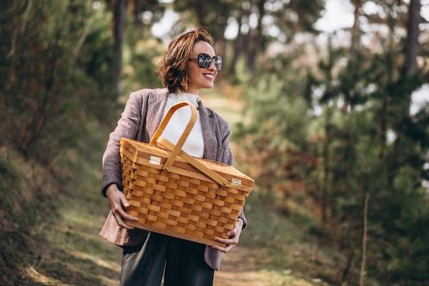 Jonge vrouw met picknickdoos in het bos