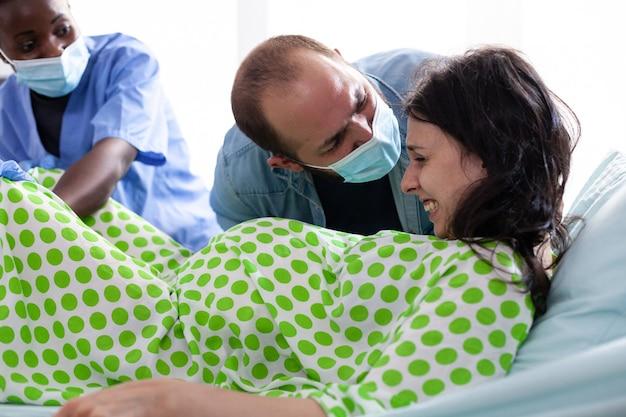 Jonge vrouw met pijn die aandringt op bevalling tijdens kraamtijd