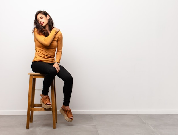 Jonge vrouw met pijn in de rug, zittend op een stoel naast copyspace