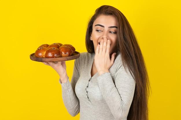 Jonge vrouw met plaat van vers gebak die zich over gele muur bevindt.