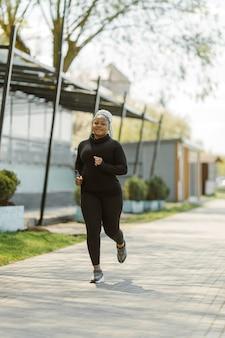 Jonge vrouw met plezier buiten trainen. sportieve mensen levensstijl concept. vrouw in sportkleding joggen