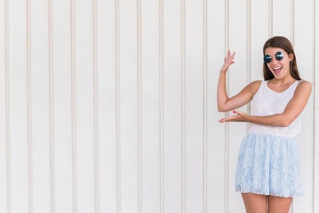 Jonge vrouw met plezier en poseren op witte muur