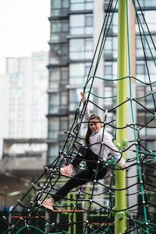 Jonge vrouw met plezier op de touwpiramide op de speelplaats