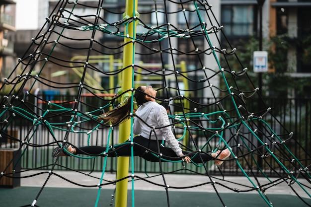 Jonge vrouw met plezier op de touwpiramide