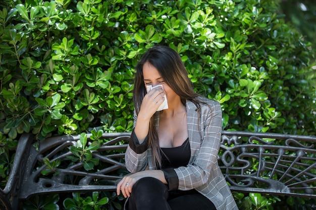 Jonge vrouw met pollenallergie die neus blaast in de buurt van bush
