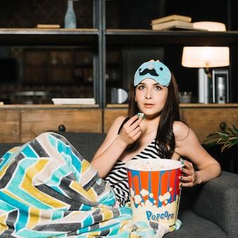 Jonge vrouw met popcorn televisiekijken