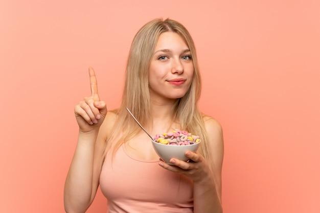 Jonge vrouw met popcorns over roze muur tellend nummer één teken