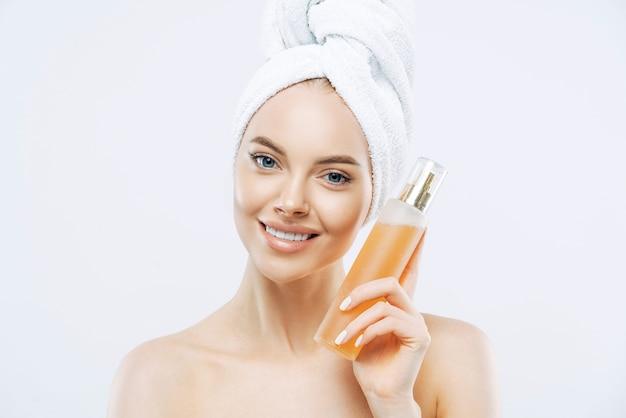Jonge vrouw met positieve glimlach, houdt grote fles aromatisch parfum met bloemgeur