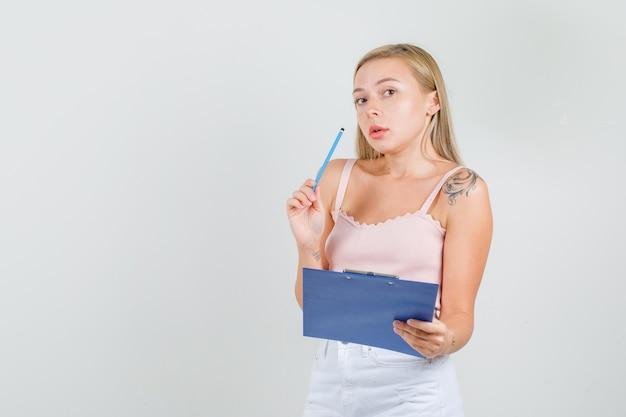 Jonge vrouw met potlood en klembord in hemd, minirok en bezig kijken