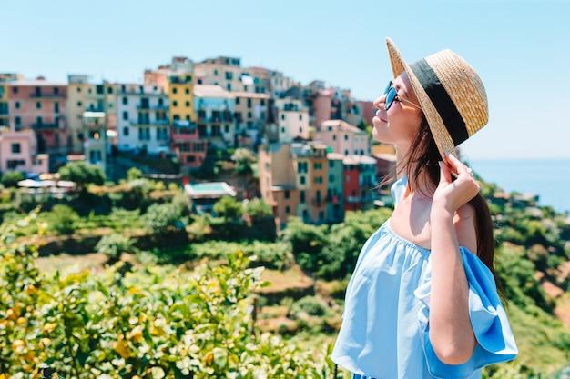 Jonge vrouw met prachtig uitzicht op het oude dorp in cinque terre, ligurië, italië. europese italiaanse vakantie.