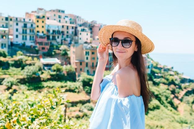 Jonge vrouw met prachtig uitzicht op het oude dorp in cinque terre, ligurië, italië.