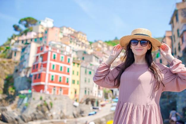 Jonge vrouw met prachtig uitzicht op het oude dorp riomaggiore, cinque terre, ligurië