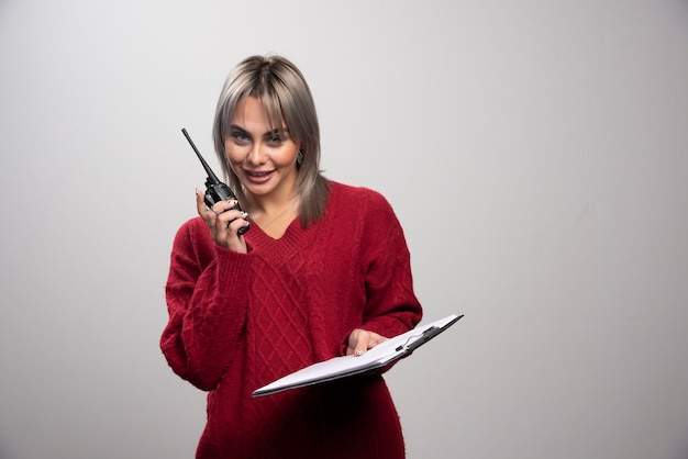 Jonge vrouw met radio transceiver en klembord poseren op grijze achtergrond.